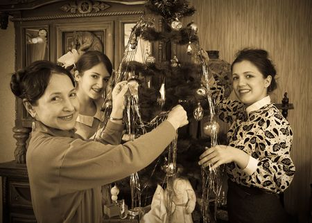Retro photo of Teen girls with mother decorating Christmas tree at home