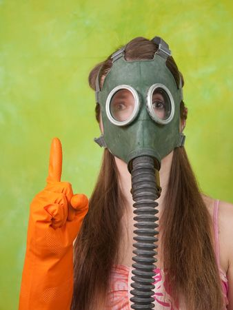 girl in gas mask pointing ATTENTION over green background