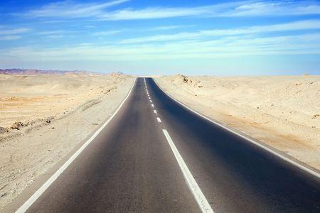 Road through desert landscape under cloudy sky