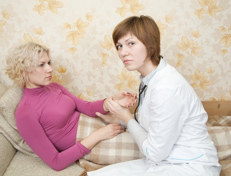 girl has her pulse taken by a caring female doctor on bed