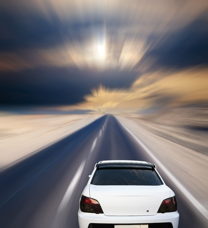 White car on desert road under blue sky