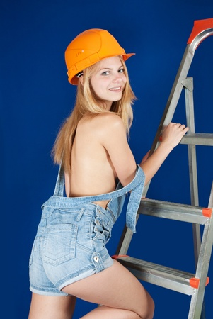 Sexy  female  builder  on stepladder over blue