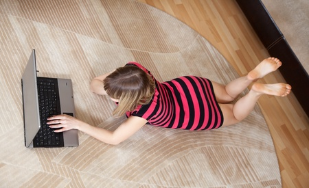 top view of young girl lying on floor and using laptop