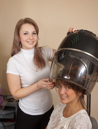 Female hairdresser working with hair dryer