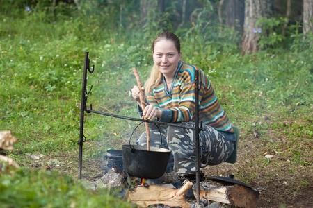 Female tourist cooking fresh food in cauldron at camp on open fire
