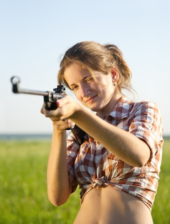 girl  aiming a pneumatic rifle  against summer field