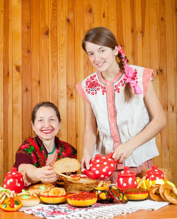 Women in traditional  clothes with pancake during  Shrovetide