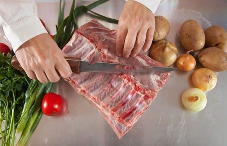 cook hands cutting raw meat at kitchen table