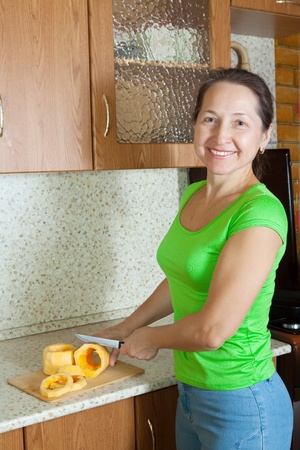 woman slicing vegetable marrow  on cutting board in her kitchen.See in series stages of cooking of stuffed vegetable marrow