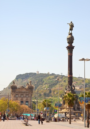 BARCELONA, SPAIN - APRIL 12: Tourists walking near Columbus monument in April 12, 2011 in Barcelona, Spain.  Columbus Monument is 60 m. It is located at finish La Rambla and built in 1888