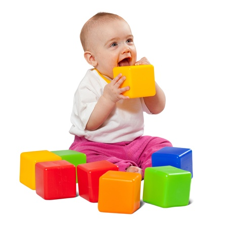 Happy baby girl plays with toy blocks over white background