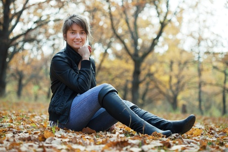 Girl in jacket and black knee-high boots at autumn park