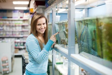 Woman chooses  fish in tank at petshop