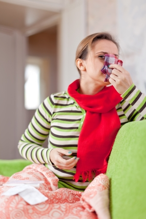 sick woman uses handkerchief in home