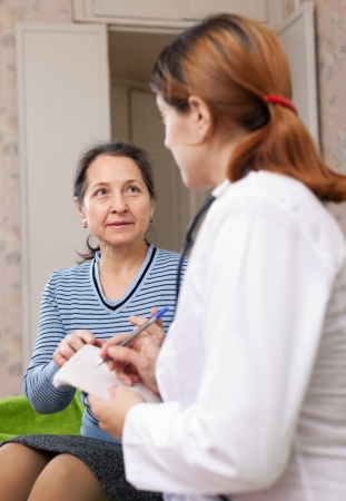 mature woman complaining to doctor about feels at home. Focus on patient