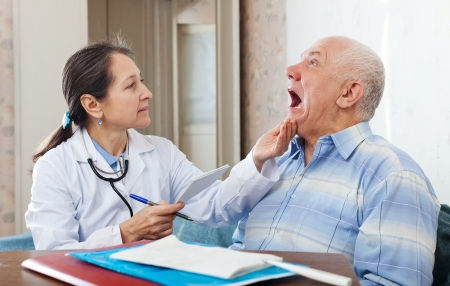 Female mature doctor looks the mouth of senior patient in clinic