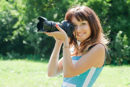 Young female photographer with camera outdoor