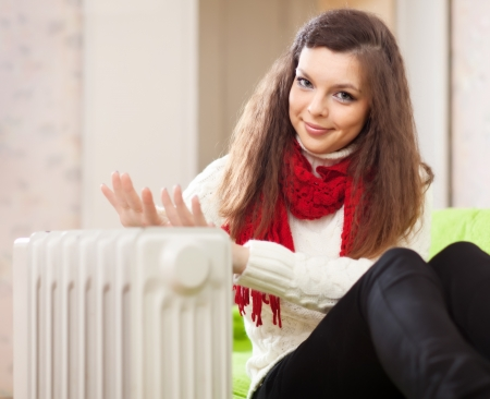Smiling woman warms hands near radiator at home