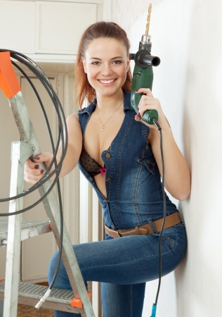 Photo pour  young happy sexy woman in overalls with drill on stepladder in the interior - image libre de droit
