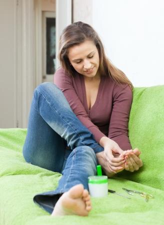 beauty woman treats her toenails at home