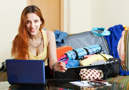 Female tourist buying tickets or reserving hotel online in the internet using laptop