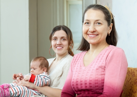 happy mature grandmother with  young mother with little baby on background