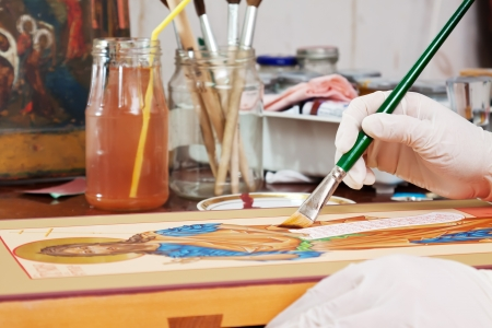 Closeup of Icon-painter makes new icon at icon painting workshop