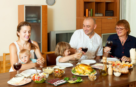 Portrait of happy family together over dining table eating chicken with wine at home interior