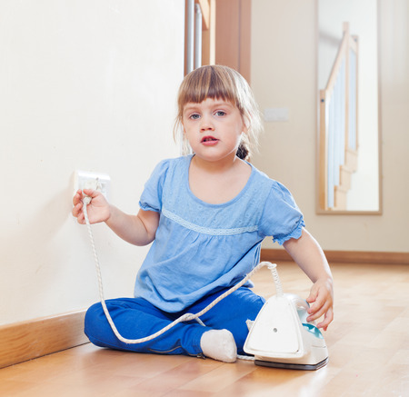 three year old child playing with electric iron