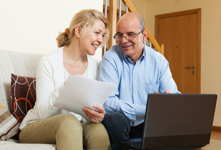 Happy mature couple with financial documents and notebook in home interior