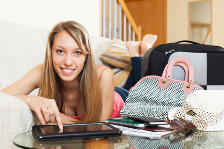 Attractive long-haired female laying on couch with tablet in hands near packed baggage