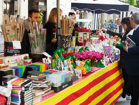 BARCELONA, SPAIN - APRIL 23, 2014: Sant Jordi feast in Catalonia, Spain.Books and red roses during Sant Jordi is traditionally in festivals