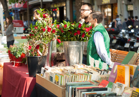 BARCELONA, SPAIN - APRIL 23, 2014: Sant Jordi is Catalan feast day of Saint George in Barcelona.Books and red roses traditionally gifts of festival
