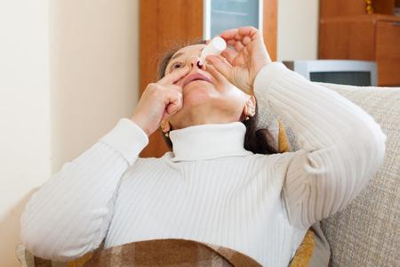 Senior woman dripping nasal drops at home