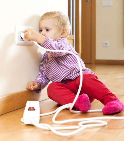 Baby girl playing with electrical extension and outlet  at home