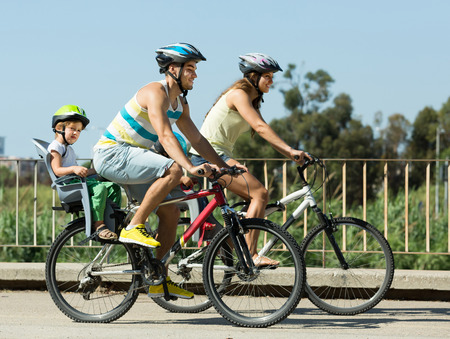 Active young family with two little daughters traveling by bicycles. Focus on man