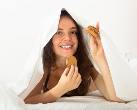 Smiling young woman eating sweet cookies on white sheet in bed