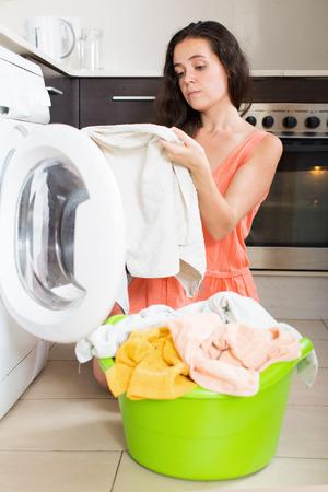 Unhappy  woman using washing machine at home