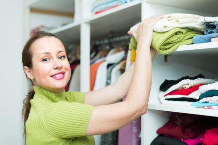Photo pour Smiling middle-aged female customer choosing apparel on shelves at store - image libre de droit