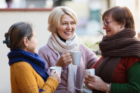 Photo pour Smiling mature female in warm clothes having cup of hot tea on terrace - image libre de droit