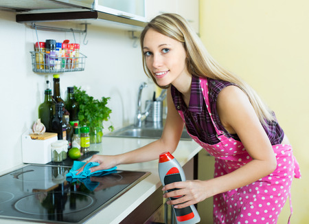 Smiling blonde girl cleaning electric panel with rag and cleanser