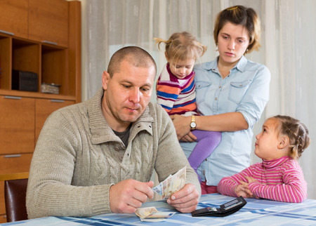 Financial problems in family. Sad woman wit children against husband at home with money
