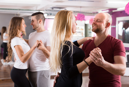 Group of positive smiling young adults dancing salsa at dance class