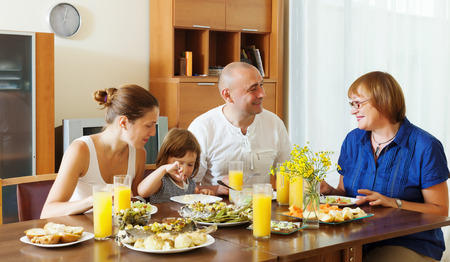 multigeneration family  eating fish with vegetables at home together
