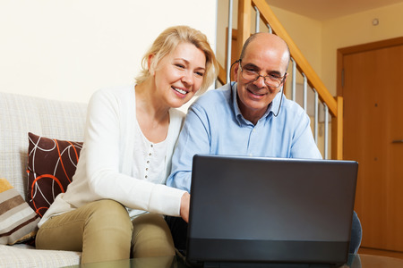 Photo pour Mature couple with laptop at table at home - image libre de droit