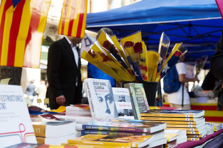 BARCELONA, SPAIN - APRIL 23, 2015:  Books on street stalls in Barcelona, Catalonia.Books and red roses - symbols of Sant Jordi feast