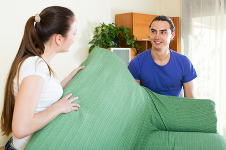 Happy couple doing relocation of furniture at living room