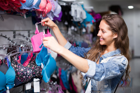 Smiling girl selecting underwear in shopping center