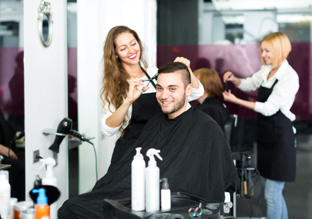 Beautiful hairdresser making a stylish haircut with sharp scissors for a man in a hair studio