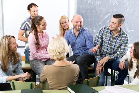 Male teacher and adult students during break in classroom